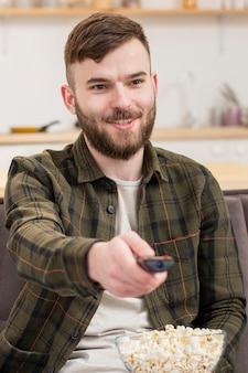 Ritratto del maschio astuto che guarda tv