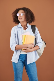 Portrait of smart teenage school student with backpack holding many books she took in library
