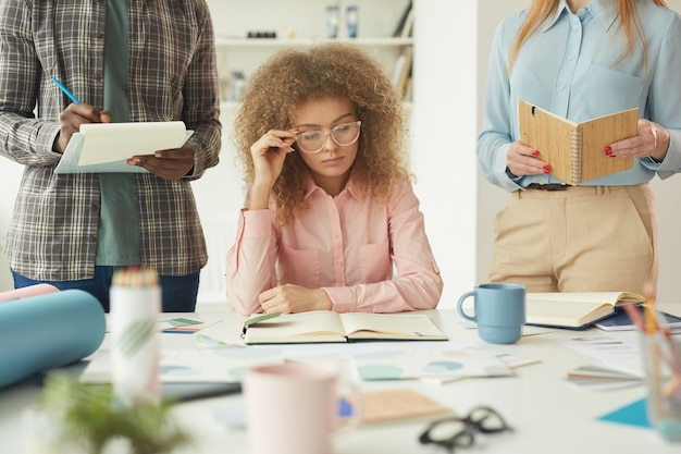 Portrait of smart young woman wearing big glasses reading notes in planner while working on business project with creative team, copy space