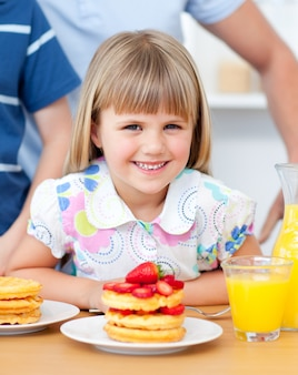 Portrait of a smiiling little girl eating waffles with strawberries