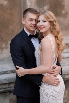Portrait of smiled couple in elegant dress and black tuxedo near stone wall
