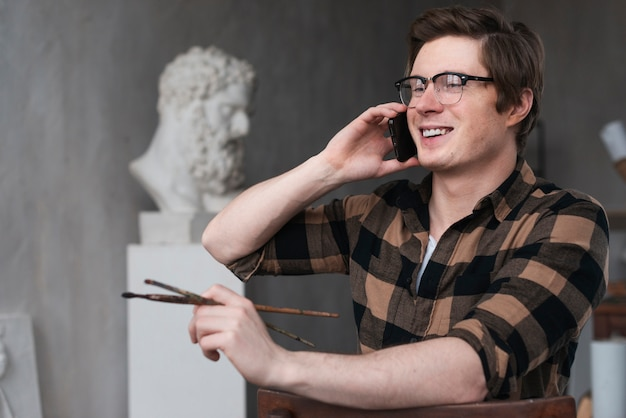 Portrait of smiley artist talking on the phone