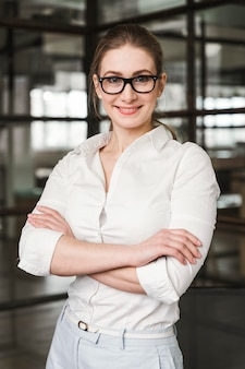 Portrait of smiley businesswoman indoors with arms closed
