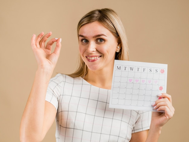 Portrait of  smiley female holding menstruation calendar