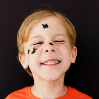 Portrait of smiley kid with face painted for halloween