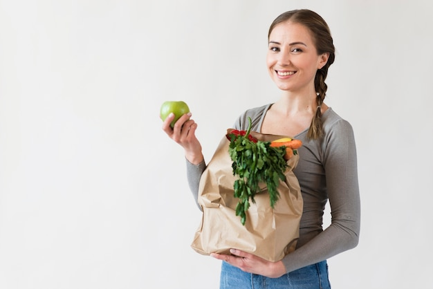 Portrait of smiley woman holding bag with fruits and vegetables