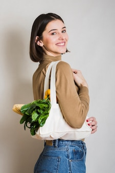 Portrait of smiley woman holding ecological groceries