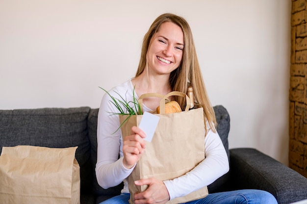 Portrait of smiley woman holding groceries bag