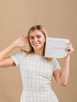 Portrait of a smiley woman holding the period calendar