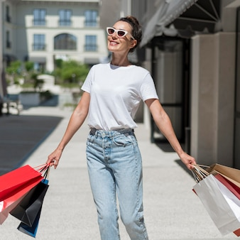 Ritratto di donna sorridente che cammina con le borse della spesa