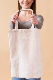 Portrait of smiley young woman holding a reusable bag
