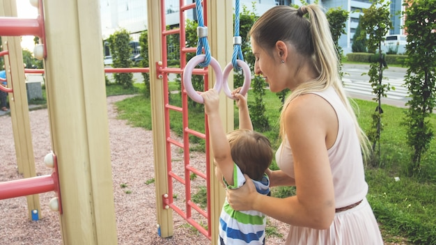 Portrait of smiling 3 years old little boy doing pull ups on rings at sports playground while mother holding and suporting him