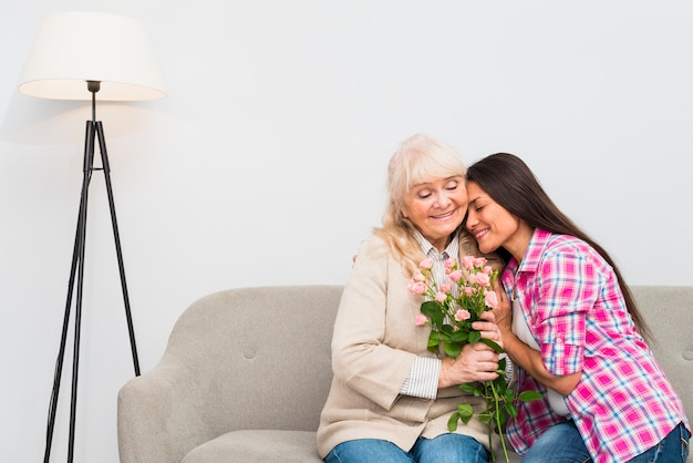 Portrait of smiling adult daughter embracing her happy senior mother holding flower bouquet
