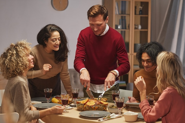 Portrait of smiling adult man cutting delicious roasted turkey while enjoying thanksgiving dinner with friends and family,