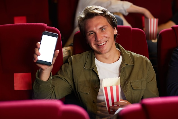 Portrait of smiling adult man holding smartphone with blank screen and looking at camera while enjoying movie in cinema theater and holding popcorn cup, copy space
