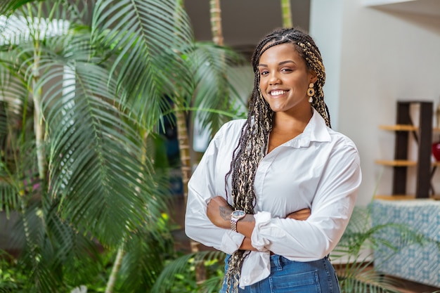 Portrait of a smiling african american adult woman standing with her arms crossed and looking at the camera. adult woman with black and yellow braids posing on a background with plants and trees.