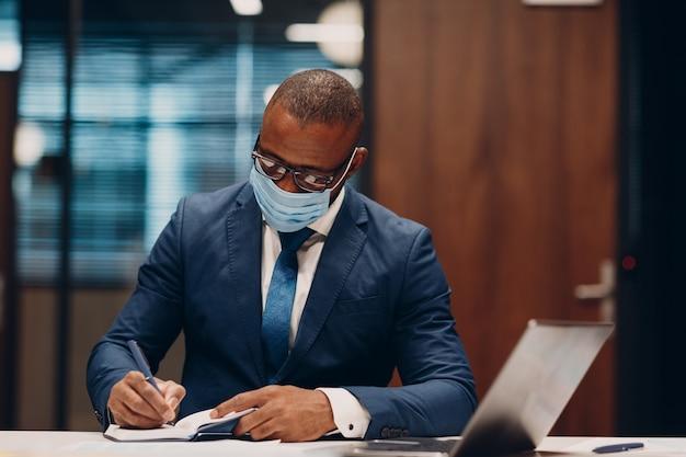 Портрет улыбающегося афро-американского бизнесмена в медицинской защитной маске сидит за столом для встречи в офисе с блокнотом с ручкой и ноутбуком