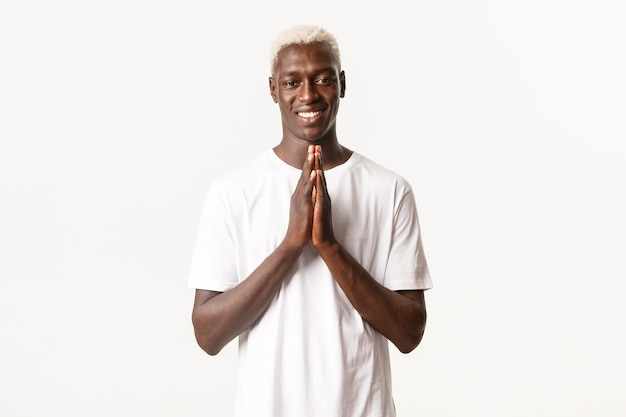 Portrait of smiling african-american handsome blond man, holding hands clasped together and looking thankful