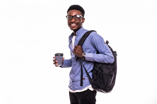Portrait of a smiling african american male college student walking with coffee isolated on white wall