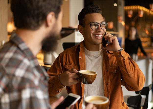 Portrait of smiling african american man talking on mobile phone. hipster friends drinking coffee together, communication, laughing, using smartphones, sitting in coffee shop. coffee break concept