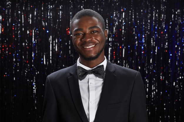 Portrait of smiling african-american man wearing tux posing at party against sprkling background, copy space
