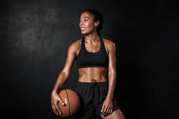 Portrait of smiling african american woman in sportswear holding basketball isolated on black