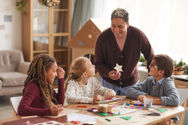 Portrait of smiling african-american woman teaching art class with multi ethnic group of children making handmade christmas cards in school