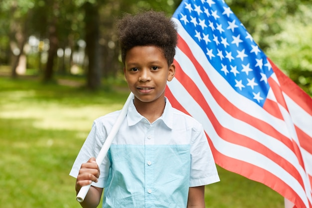 Portrait of smiling african boy carrying american flag while standing outdoors in park