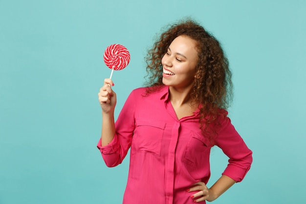Portrait of smiling african girl in casual clothes hold looking, on pink round lollipop isolated on blue turquoise background in studio. people sincere emotions, lifestyle concept. mock up copy space.