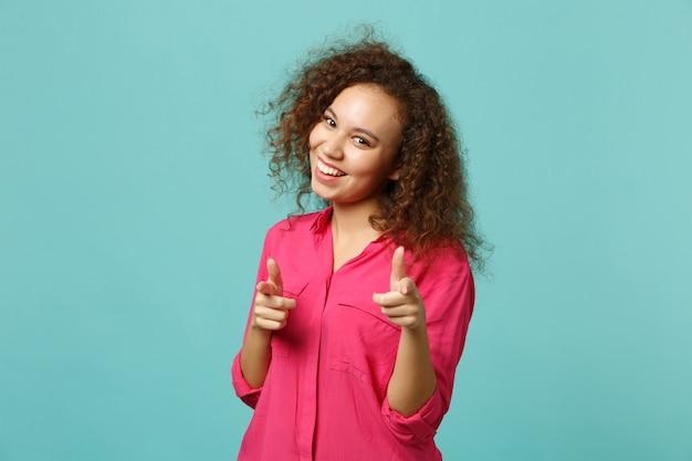 Ritratto della ragazza africana sorridente in abbigliamento casual che indica le dita indice sulla macchina fotografica isolata sul fondo blu della parete del turchese in studio. concetto di stile di vita di emozioni sincere della gente. mock up copia spazio.