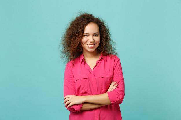 Il ritratto della ragazza africana sorridente in vestiti casuali rosa che si tiene per mano ha attraversato isolato sul fondo blu della parete del turchese in studio. persone sincere emozioni, concetto di stile di vita. mock up copia spazio.
