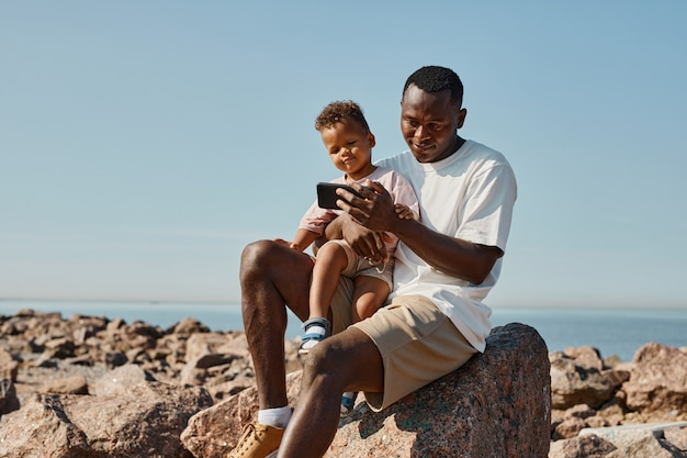 Portrait of smiling africanamerican father playing with cute son on beach copy space