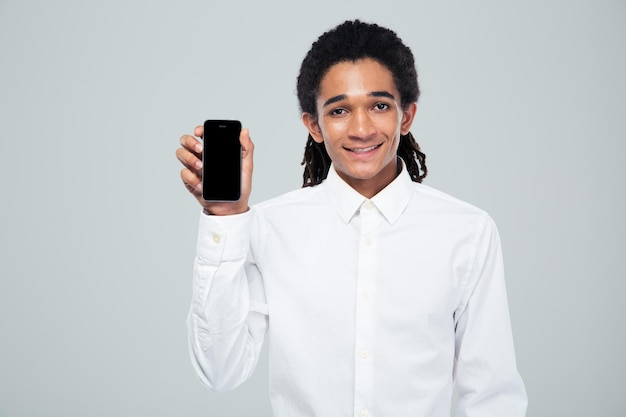 Portrait of a smiling afro american businessman showing blank smartphone screen over gray wall