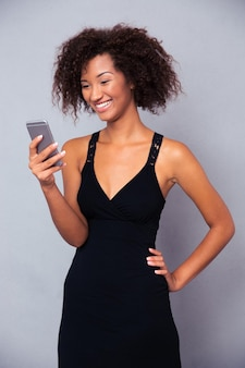 Portrait of a smiling afro american woman using smartphone over gray wall