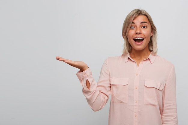 Portrait of smiling amazed blonde young woman with braces on teeth and opened mouth wears pink shirt looks surprised and holding copyspace on palm isolated over white wall