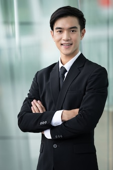 Portrait of smiling asian businessman in black suit at office outdoor