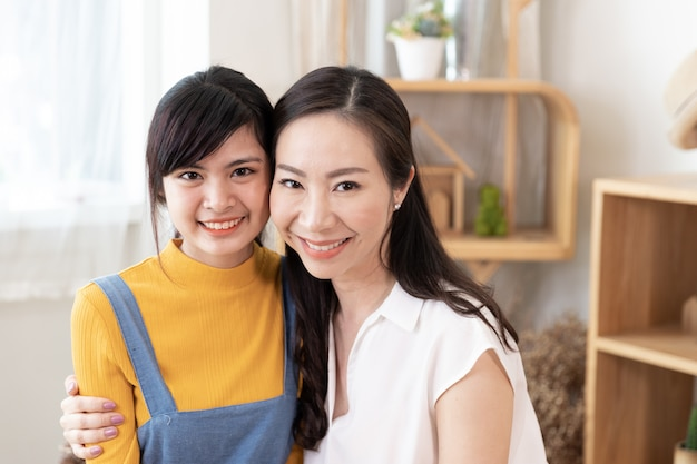 Portrait of smiling asian family mom and teenage daughter