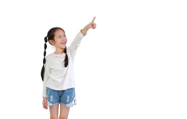 コピースペースと白い背景で隔離の肖像画笑顔アジアの小さな子供女の子人差し指