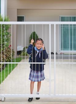 朝の学校に行く前に家のドアの柵で幼稚園の制服を着たアジアの少女の笑顔の肖像画。