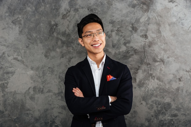 Portrait of a smiling asian man dressed in suit standing