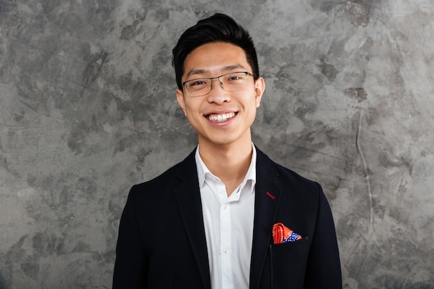 Portrait of a smiling asian man dressed in suit