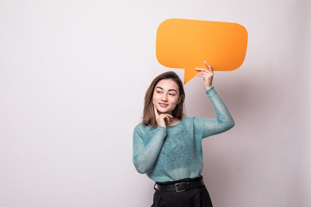 Portrait of a smiling asian woman holding empty orange speech bubble isolated over gray wall