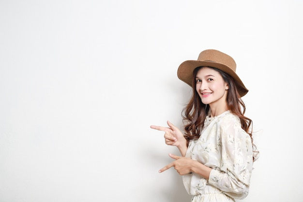 Portrait of a smiling asian woman presenter on white wall, beautiful thai girl.