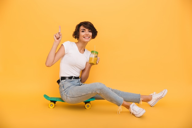 Portrait of a smiling attractive woman sitting on a skateboard