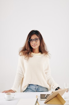 Portrait of smiling attractive young asian woman in sweater standing at desk with cup of coffee, tablet computer and textbooks prepared for online class