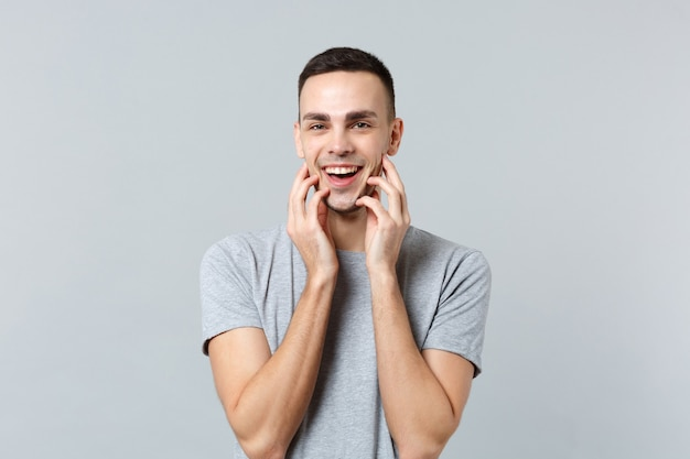 Portrait of smiling attractive young man in casual clothes putting hands on face