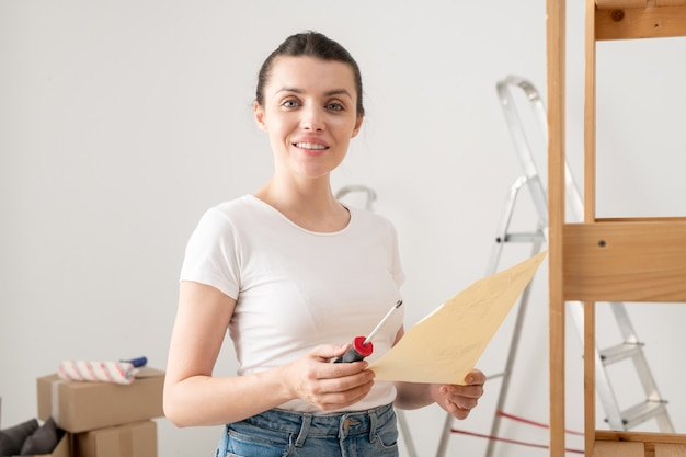 Portrait of smiling attractive young woman holding screwdriver and assembling furniture according to instruction