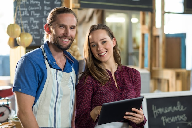 Portrait of smiling bakery staff using digital tablet at counter