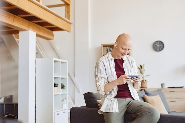 Portrait of smiling bald woman using smartphone with wireless earphones while enjoying music at home in modern interior, alopecia and cancer awareness, copy space