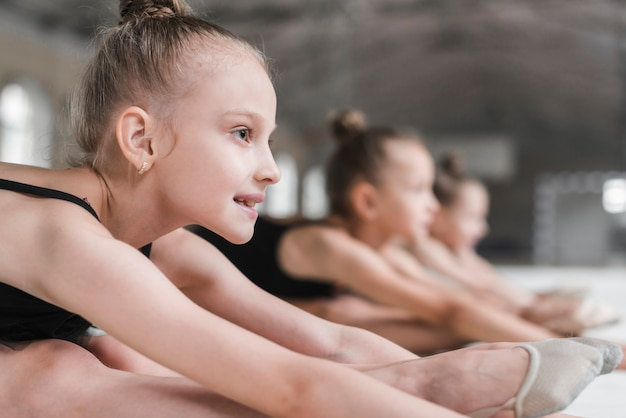 Portrait of smiling ballerina girl with her friends stretching